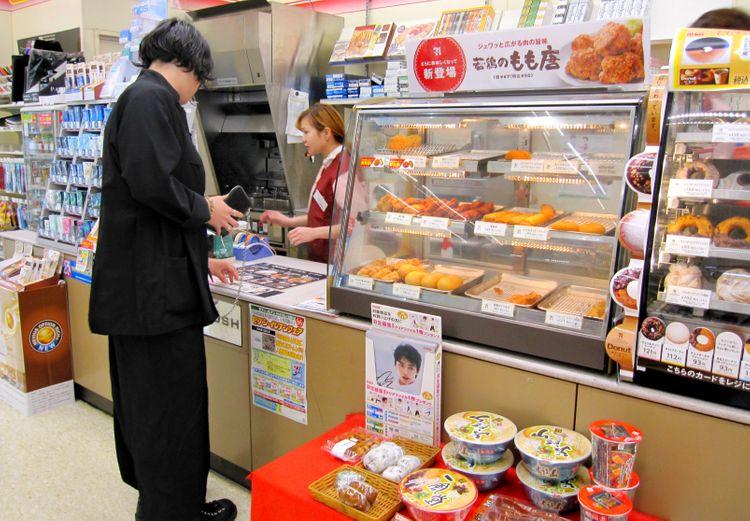man paying at convenience store japan