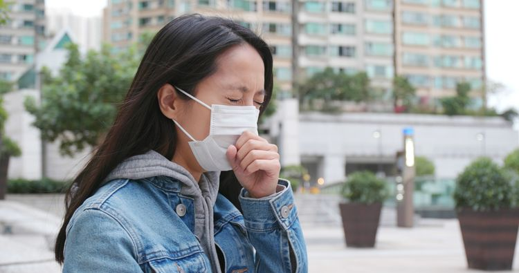 sneezing woman in mask