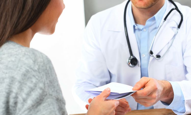 doctor passing note to patient