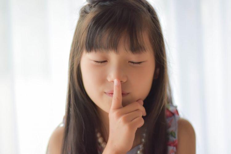 child shushing someone with eyes closed