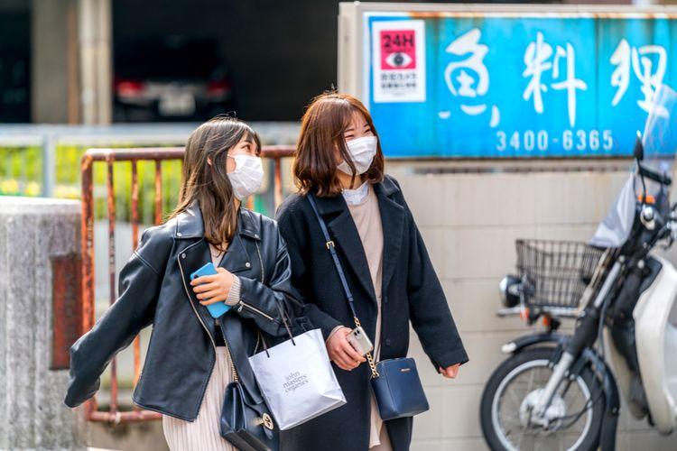 two Japanese women wearing masks