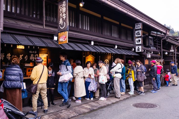 long queue outside of Sushi restaurant Japan