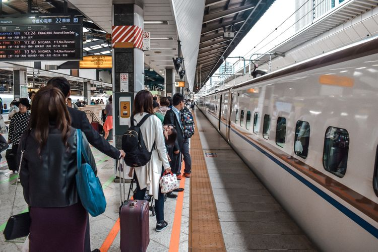 passengers lining up for shinkansen with their luggage