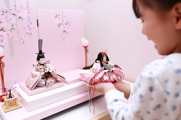 young girl playing with mebina doll