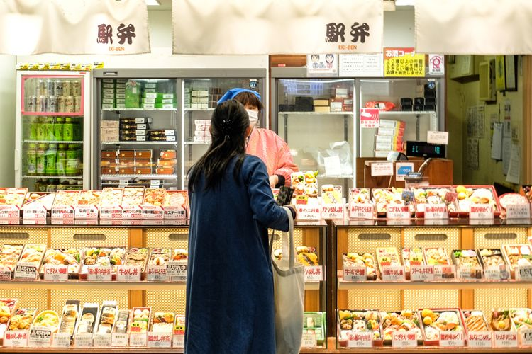 woman standing in front of bento shop