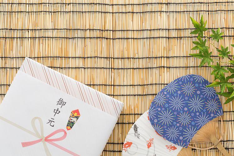 御中元的禮盒和日本扇子鋪在竹蓆上