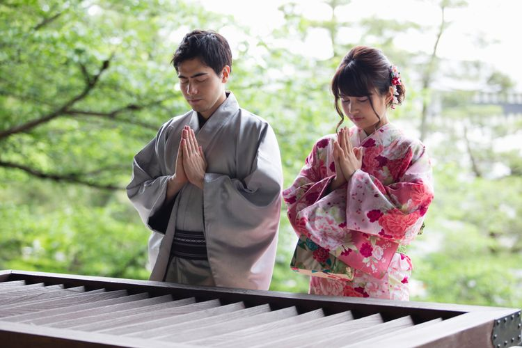 A Japanese man and woman pray at a shrine for hatsumode on new year