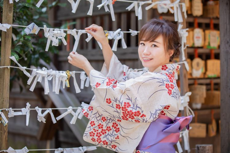 A Japanese woman in a kimono is tying an omikuji fortune
