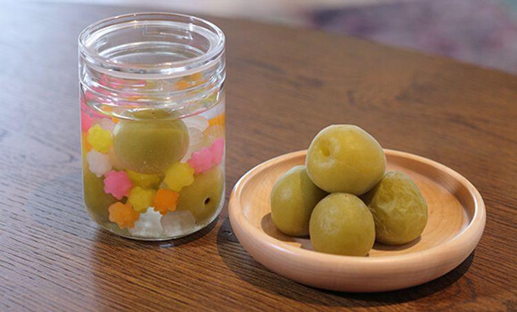 木桌上擺著擺放梅子的玻璃罐和裝著梅子的木盆