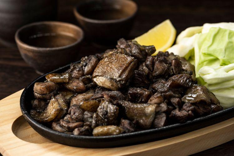 鐵盤內擺著炭火宮崎地雞和高麗菜生菜