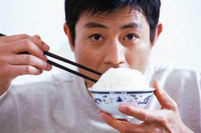 Man Eating Bowl of Rice --- Image by © Yang Liu/Corbis