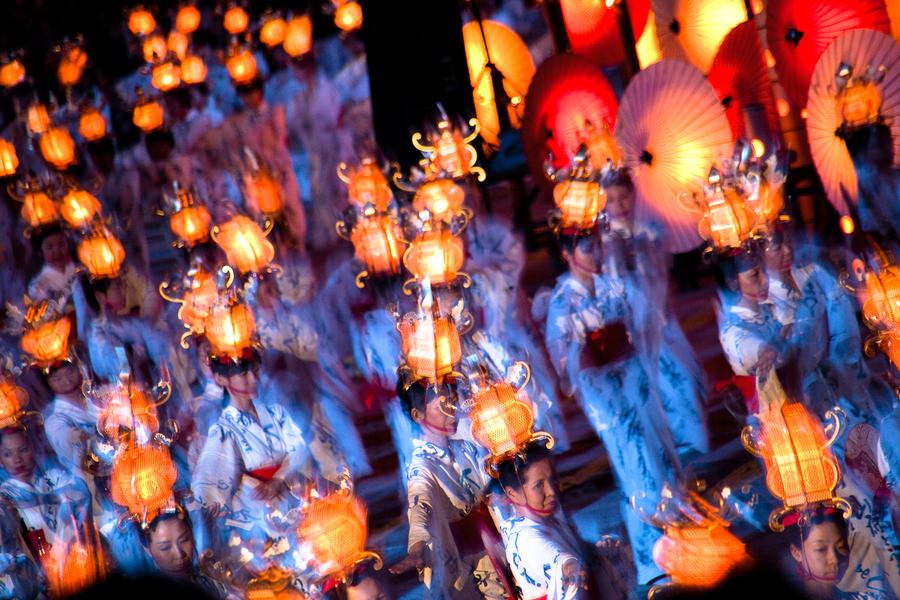 Women in Yukata and bearing a lantern.