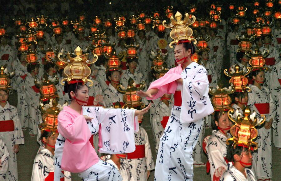 Women bearing golden lantern dancing at the Yamaga Toro Matsuri